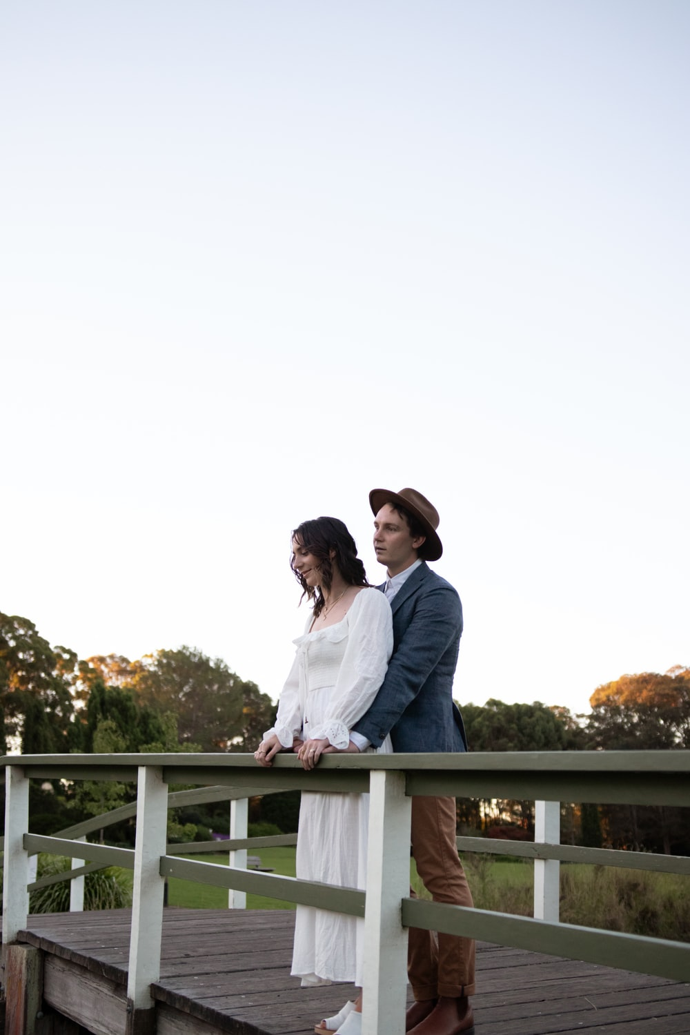 man in white dress shirt and woman in white dress standing on white wooden bridge during