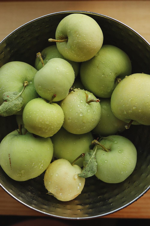 green round fruits in black plastic bucket
