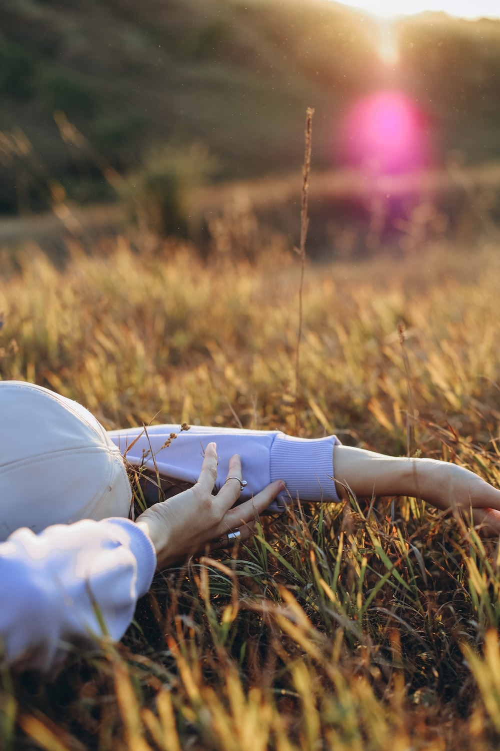 person in white long sleeve shirt and white pants sitting on green grass field during daytime