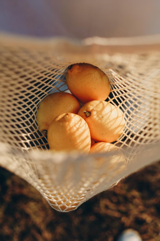 yellow round fruits on white net