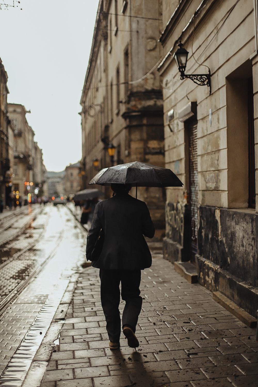 person in black coat holding umbrella walking on sidewalk during daytime