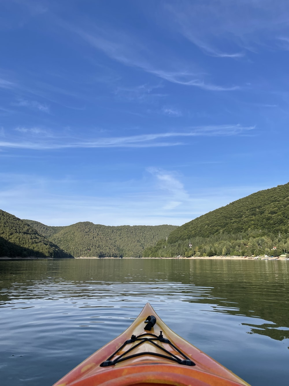 brown canoe on lake near green mountains under blue sky during daytime