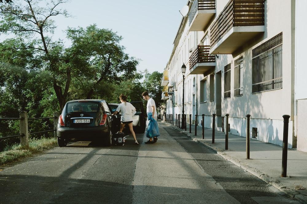 man in white t-shirt walking on sidewalk during daytime