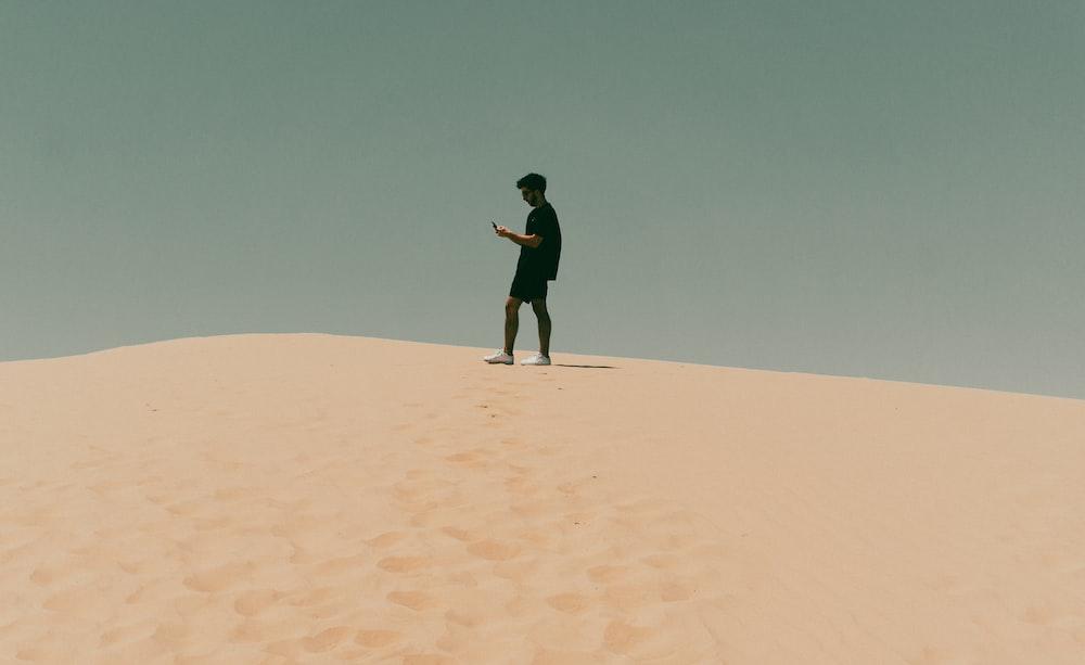 man in black jacket standing on brown sand during daytime