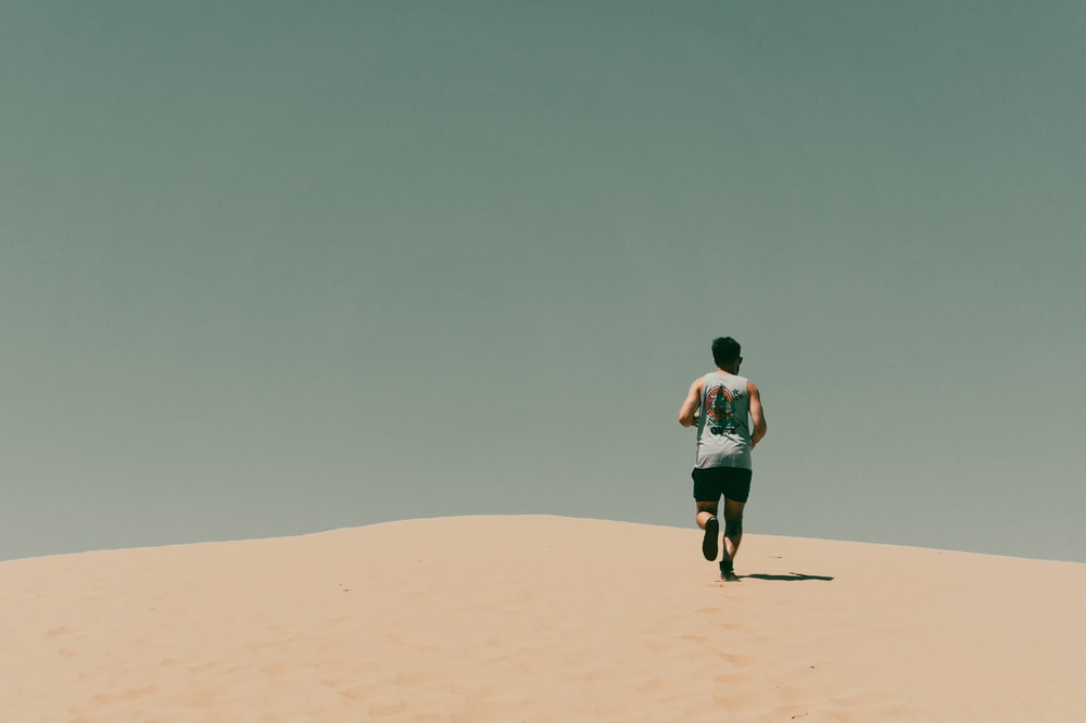 man in blue t-shirt and black shorts walking on brown sand during daytime