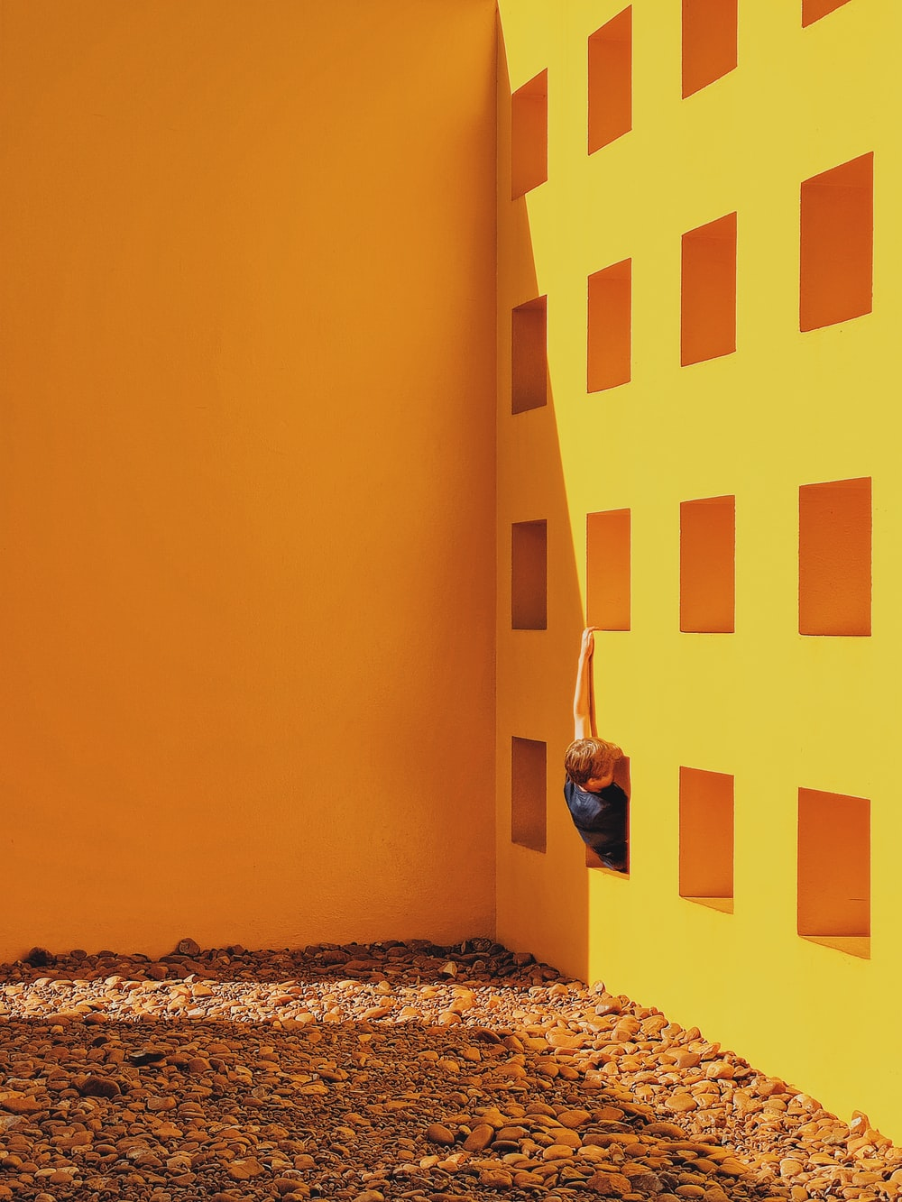 man in black jacket standing beside yellow painted wall