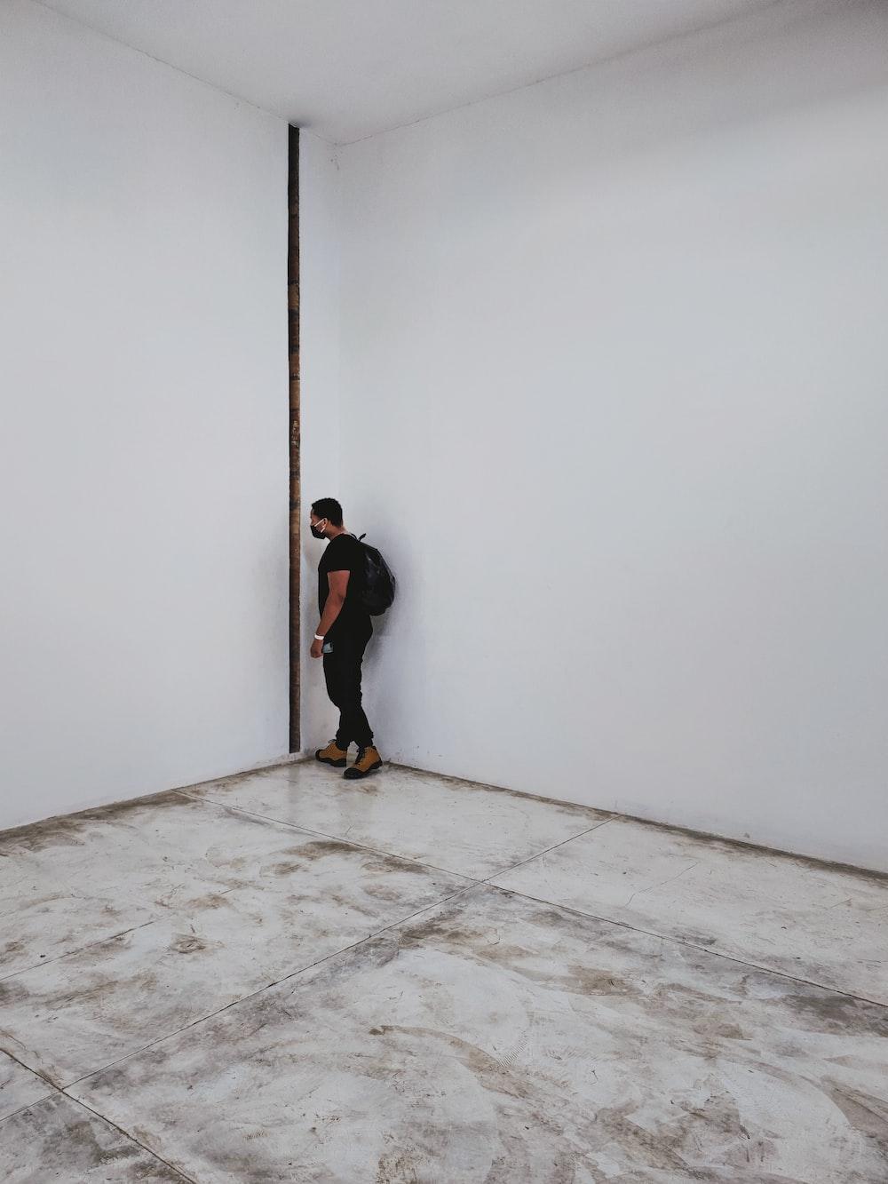 man in black jacket and black pants walking on white floor tiles