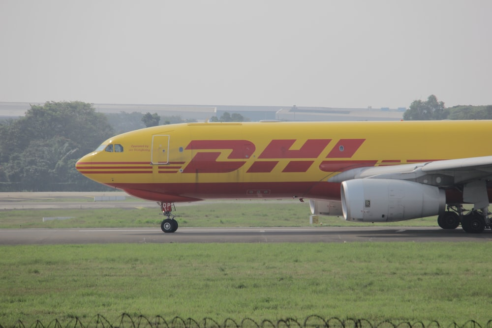 yellow and red passenger plane on airport during daytime