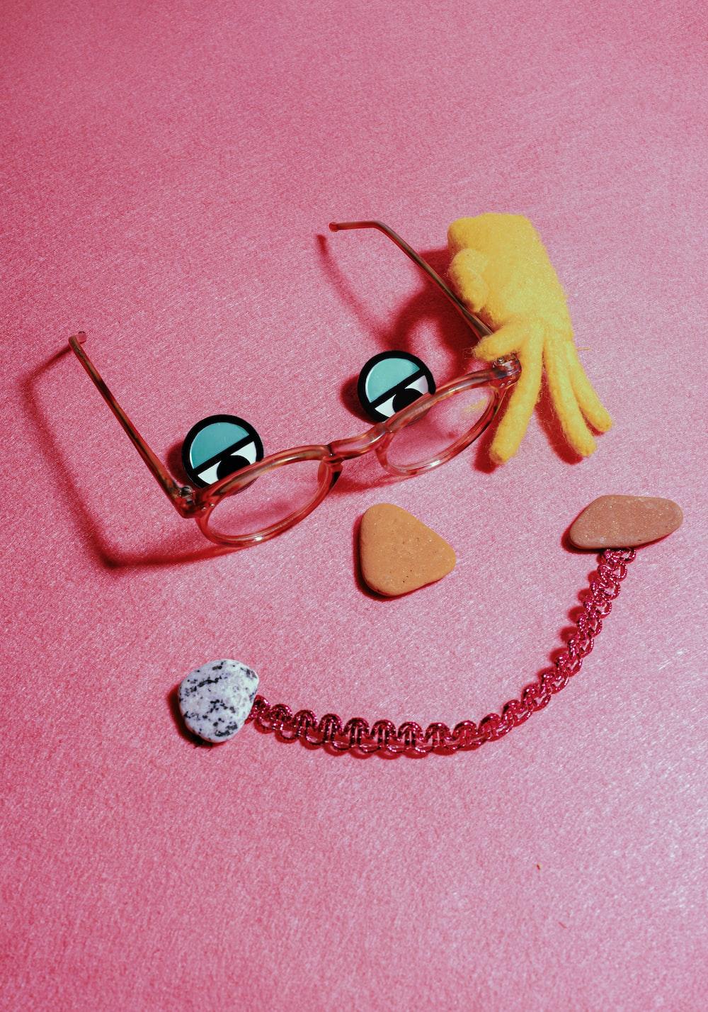 black framed eyeglasses on pink surface