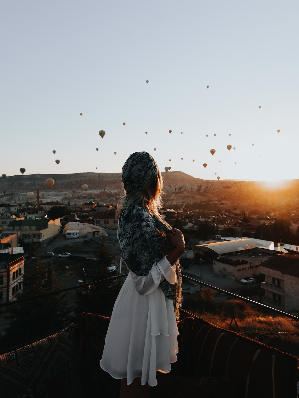 woman in white dress standing on top of building during sunset