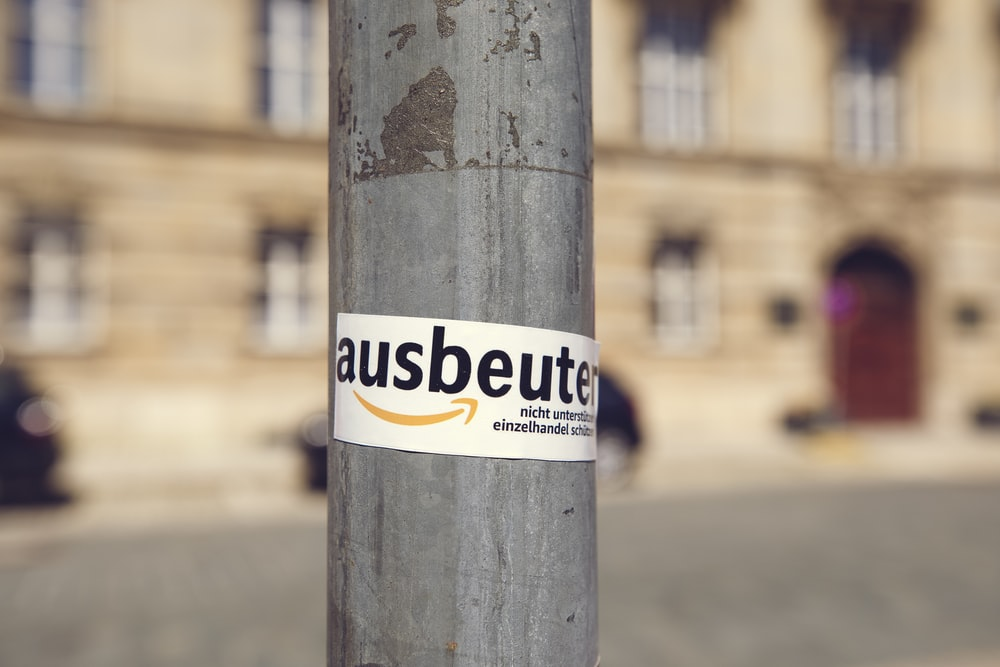 white and yellow sticker on brown wooden post