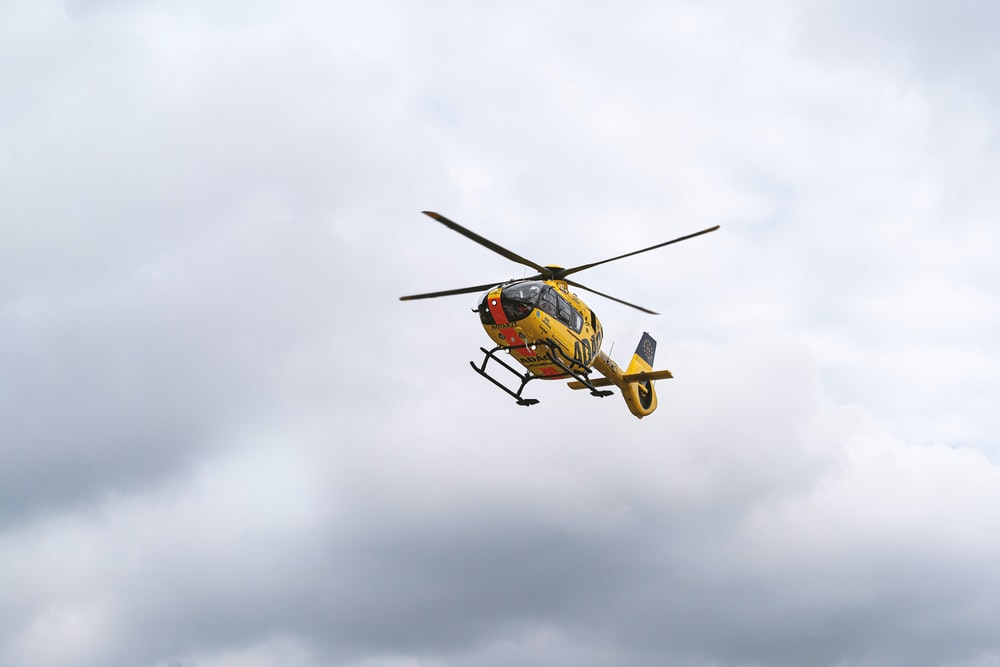 yellow and black helicopter flying in the sky