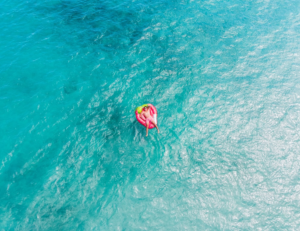 yellow and pink inflatable ring on water