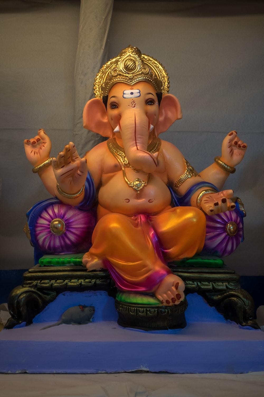 gold hindu deity figurine on blue textile