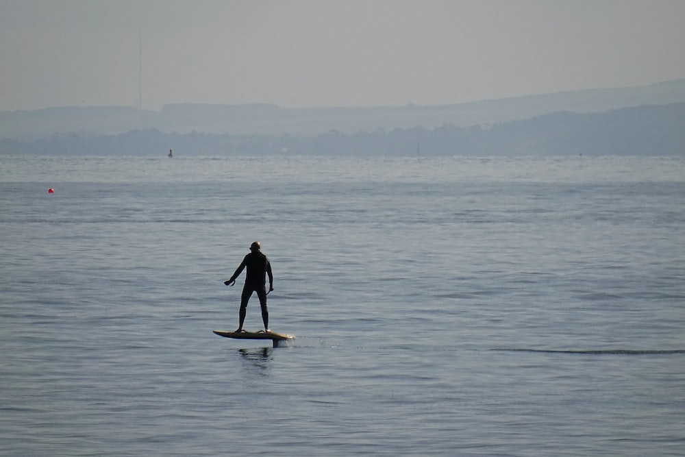 man in black wet suit standing on white surfboard on sea during daytime