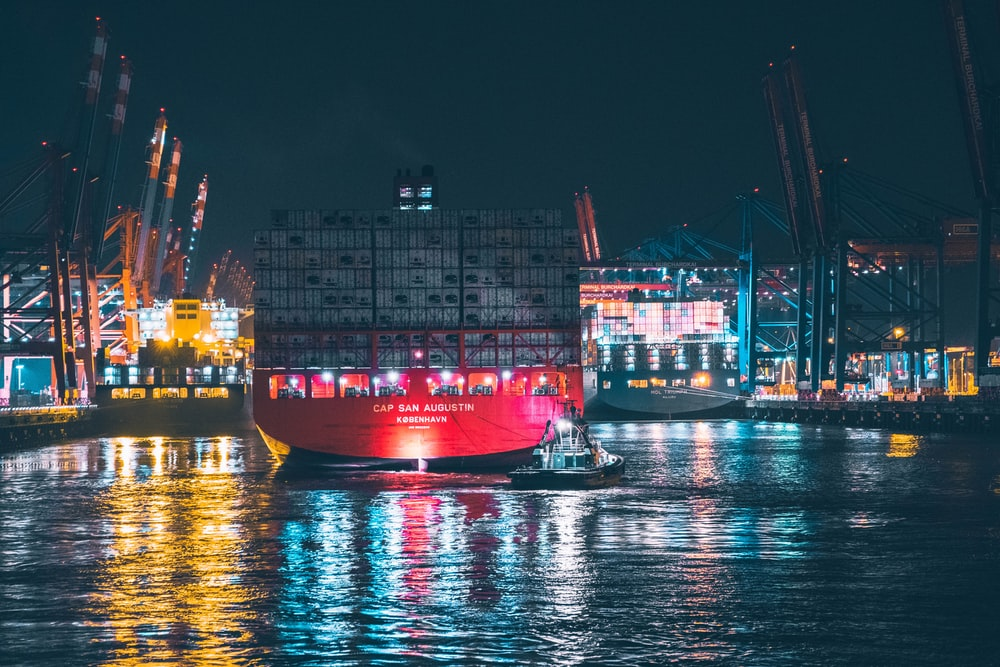 red and white cargo ship on dock during night time