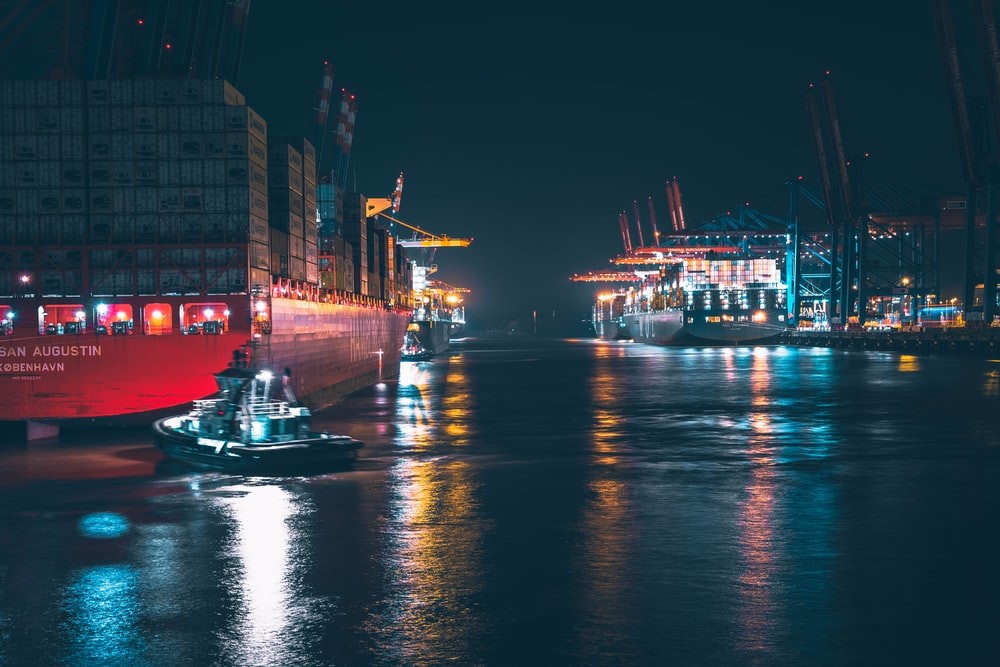 red and white boat on water during night time