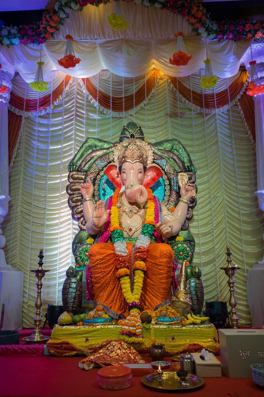 hindu deity figurine on green and white textile