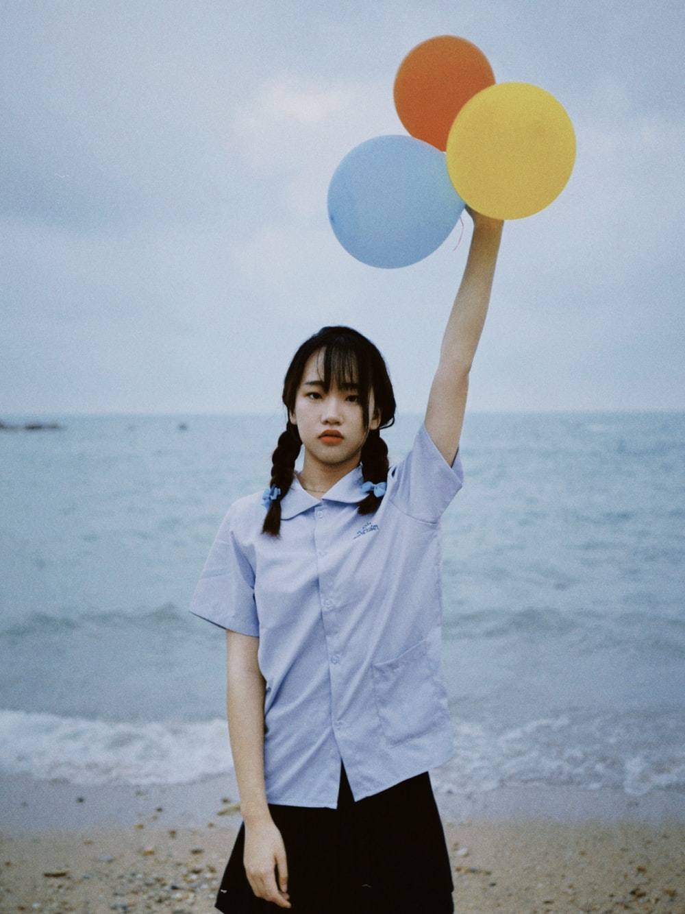 woman in white button up shirt holding blue and white balloons