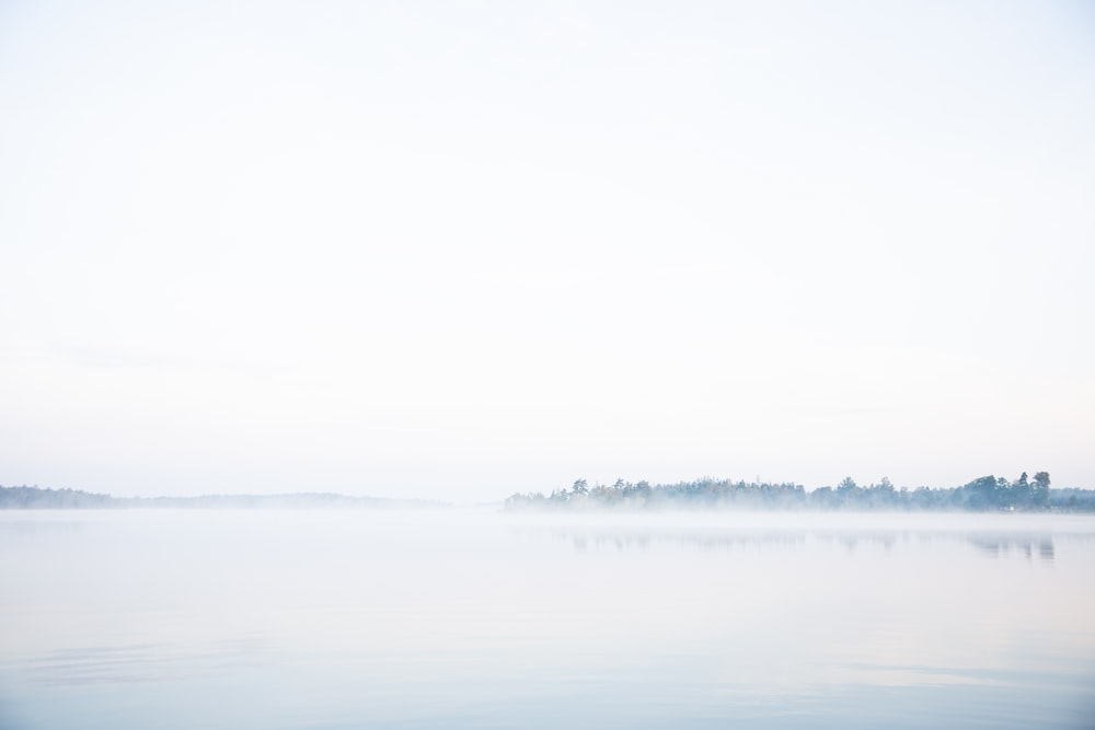 body of water under white sky during daytime