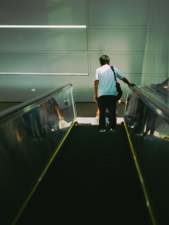 man in white shirt and black pants walking on escalator