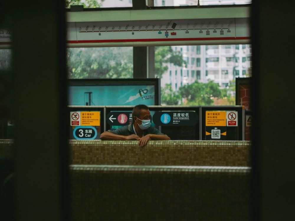 woman in blue t-shirt sitting on window