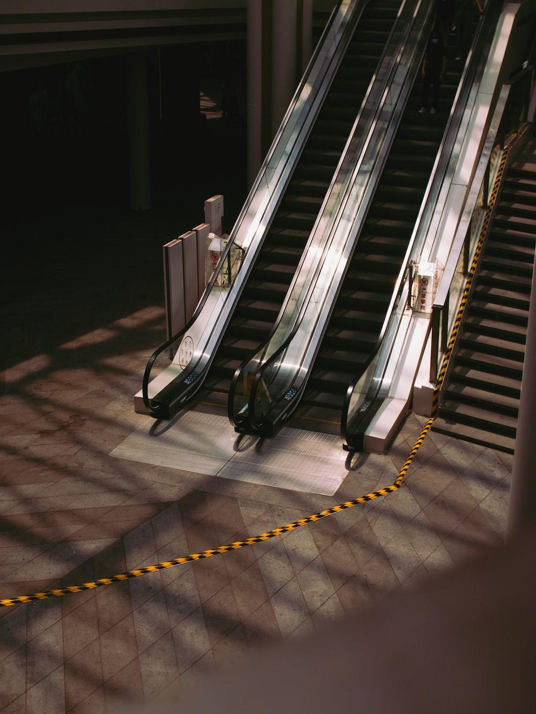 black and silver escalator on gray concrete floor
