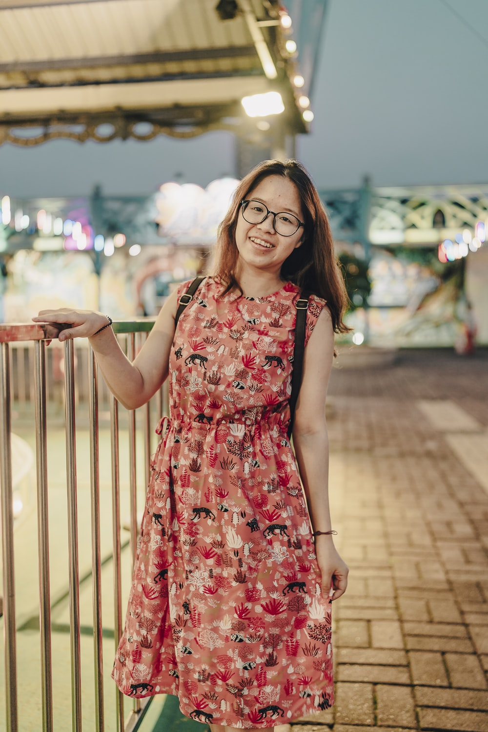 woman in red and white floral sleeveless dress standing on brown wooden bridge during daytime