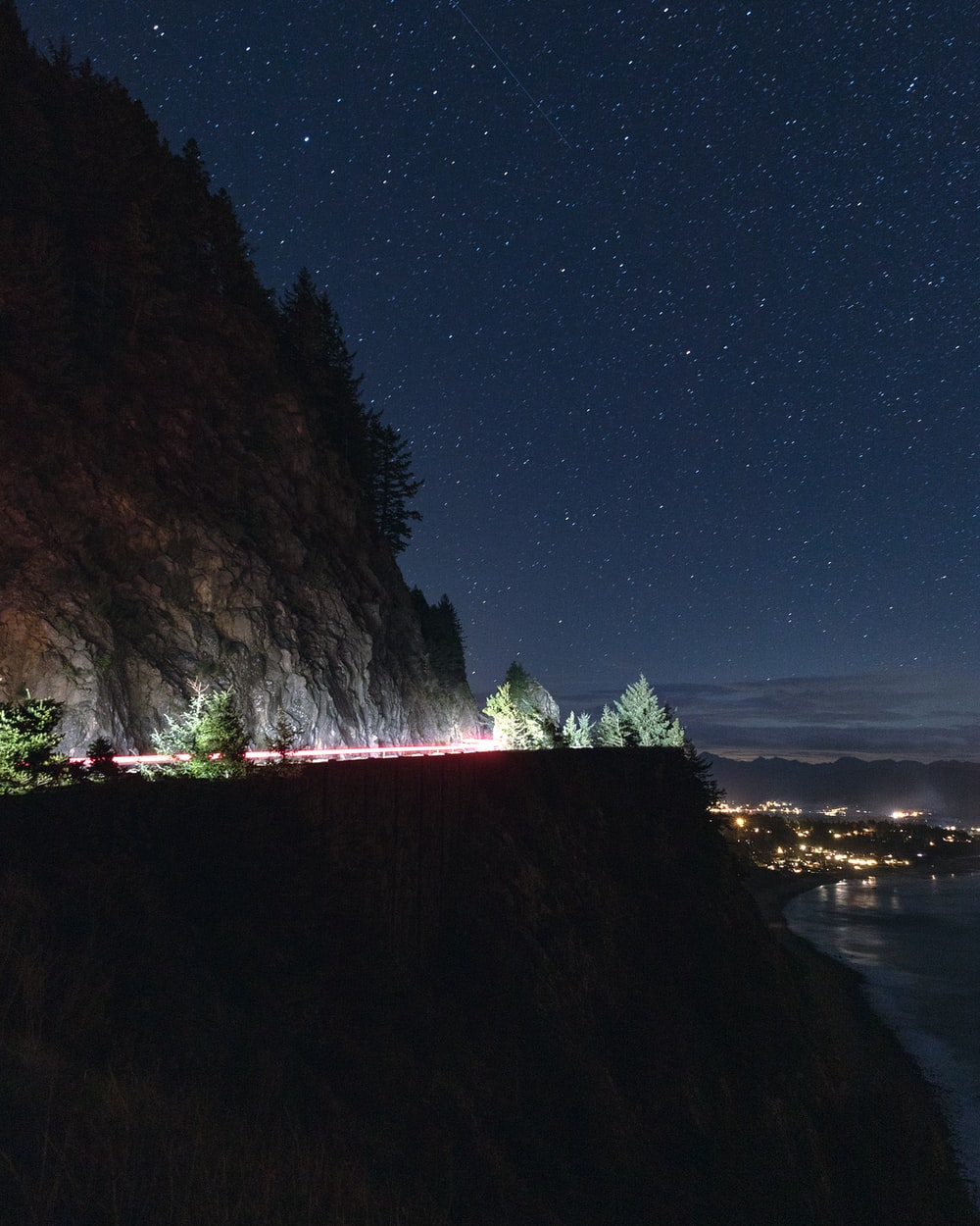brown mountain near body of water during night time