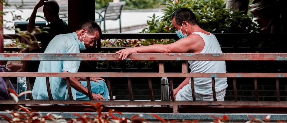 man in white tank top sitting on brown wooden bench during daytime
