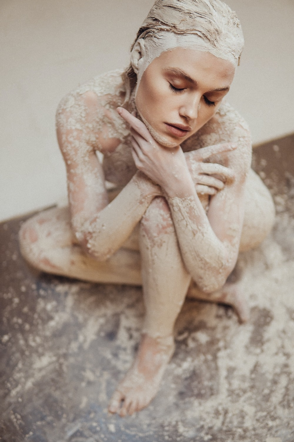 nude woman leaning on wall