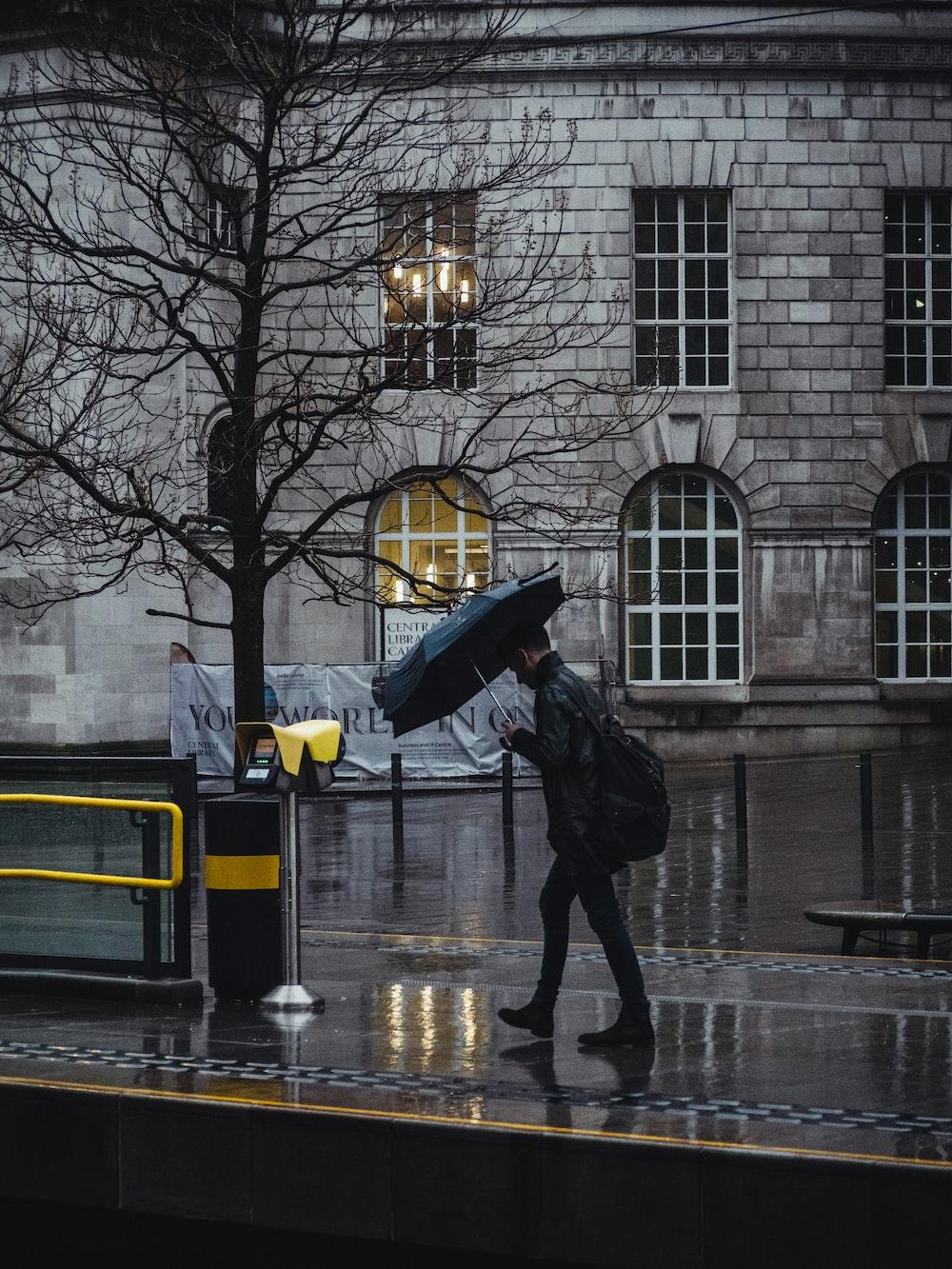 person in black jacket and black pants holding umbrella walking on sidewalk during daytime