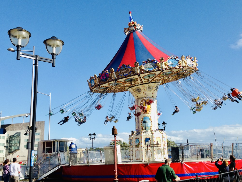 people standing on red and blue carousel during daytime