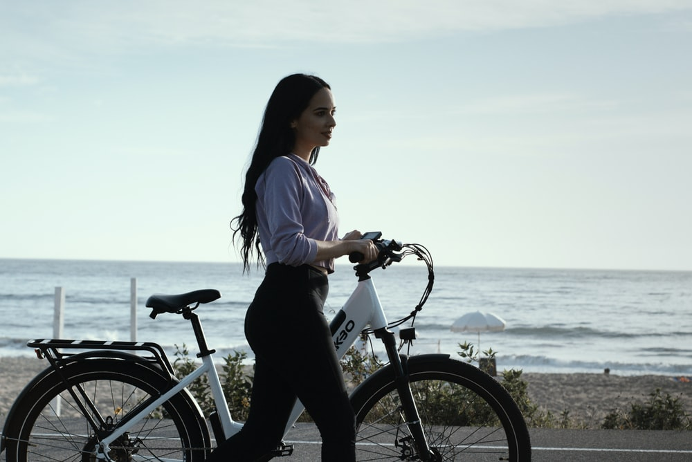 woman in white shirt and black pants riding on bicycle near body of water during daytime