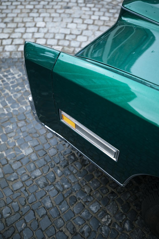 green car on gray concrete pavement