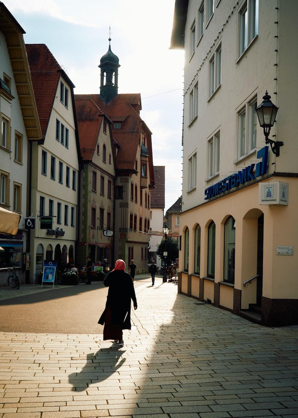 woman in black coat walking on sidewalk during daytime