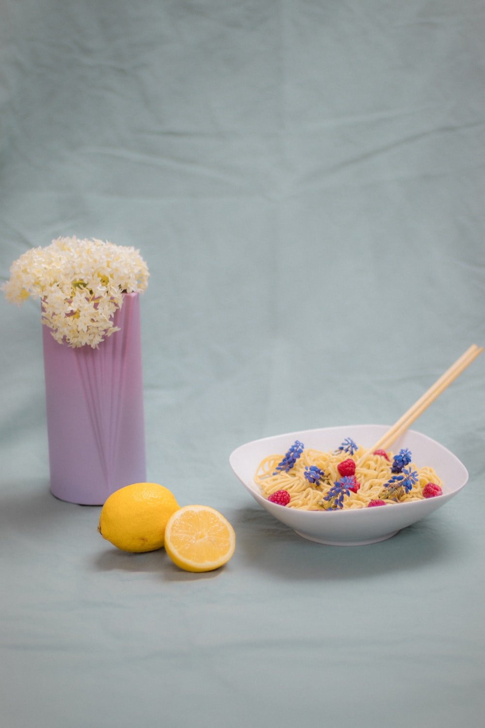 white and purple floral ceramic vase with yellow lemon and purple and white flower
