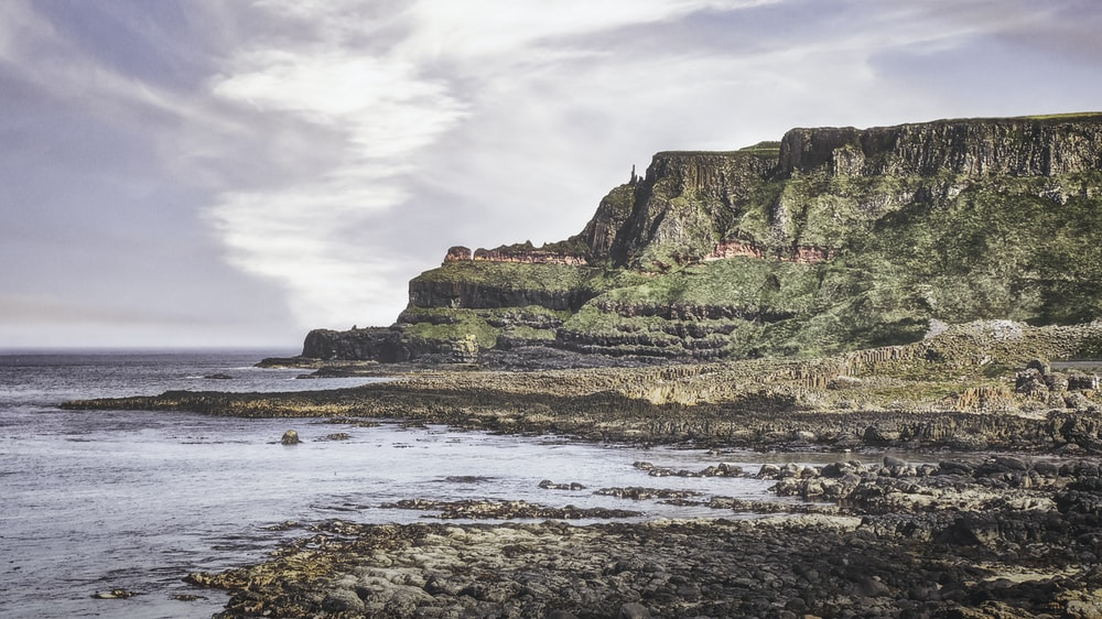 brown and green rock formation on sea shore during daytime