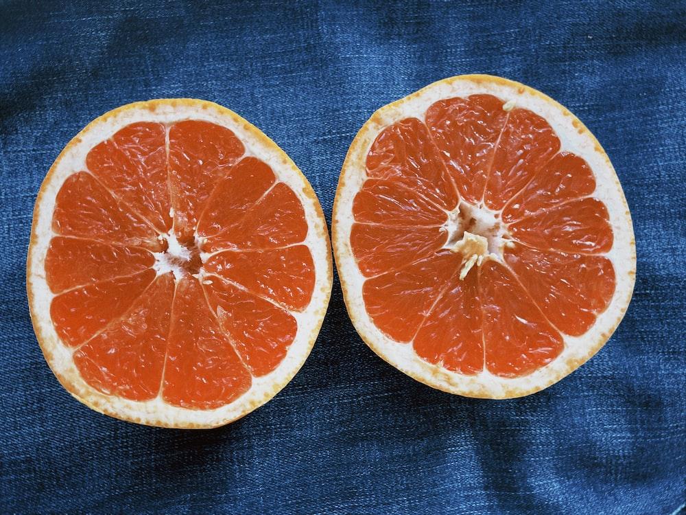 sliced orange fruit on blue textile