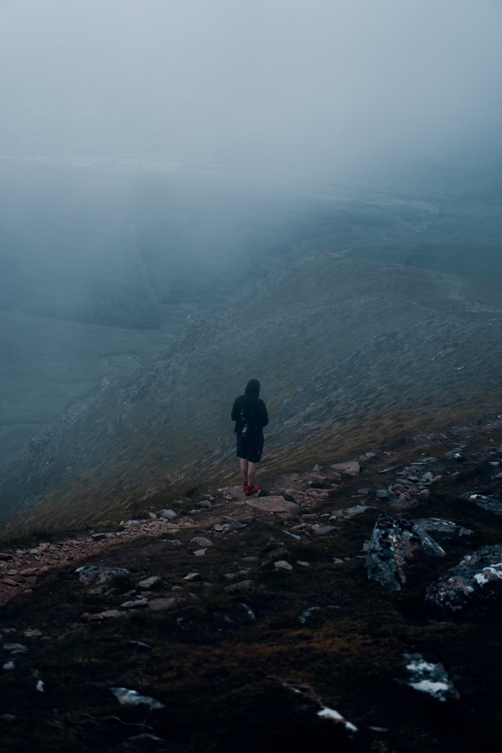 person in black jacket standing on rocky hill during foggy weather