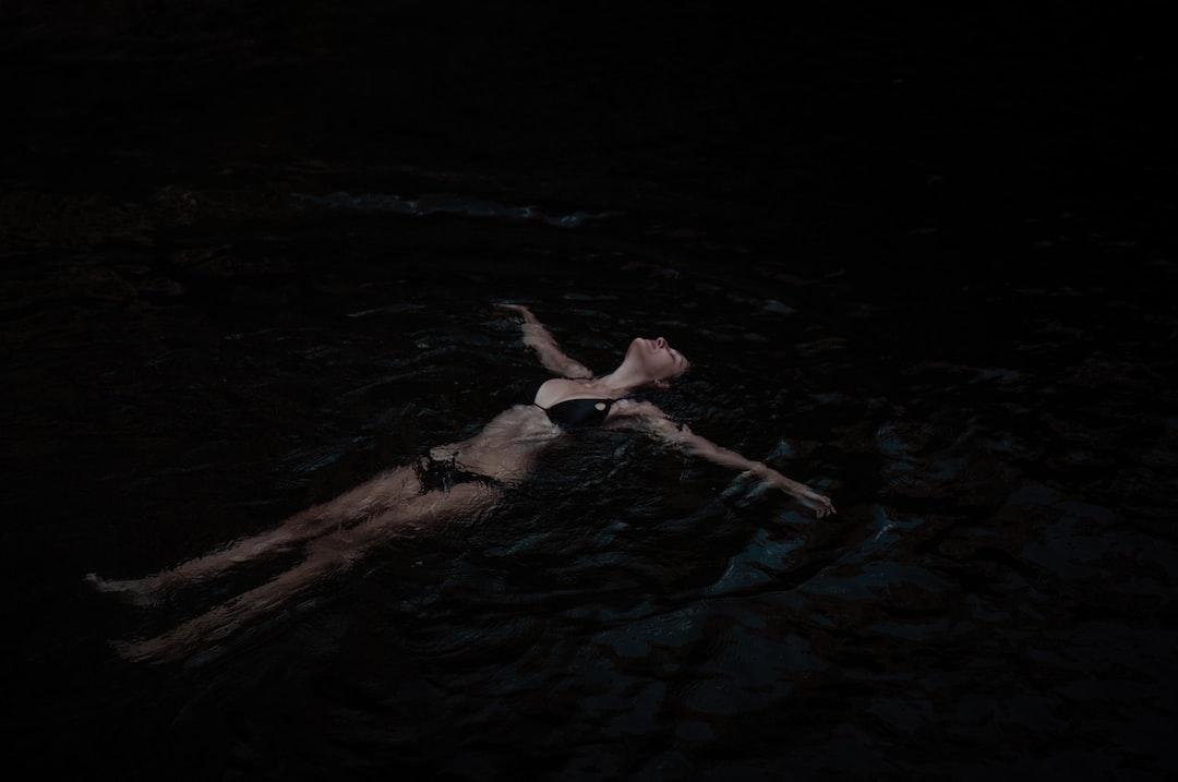 A Woman Floating In Dark Waters - unsplash