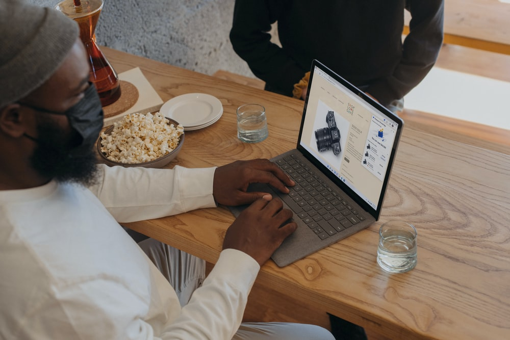 Person sitting on a table on Surface laptop wearing a mask