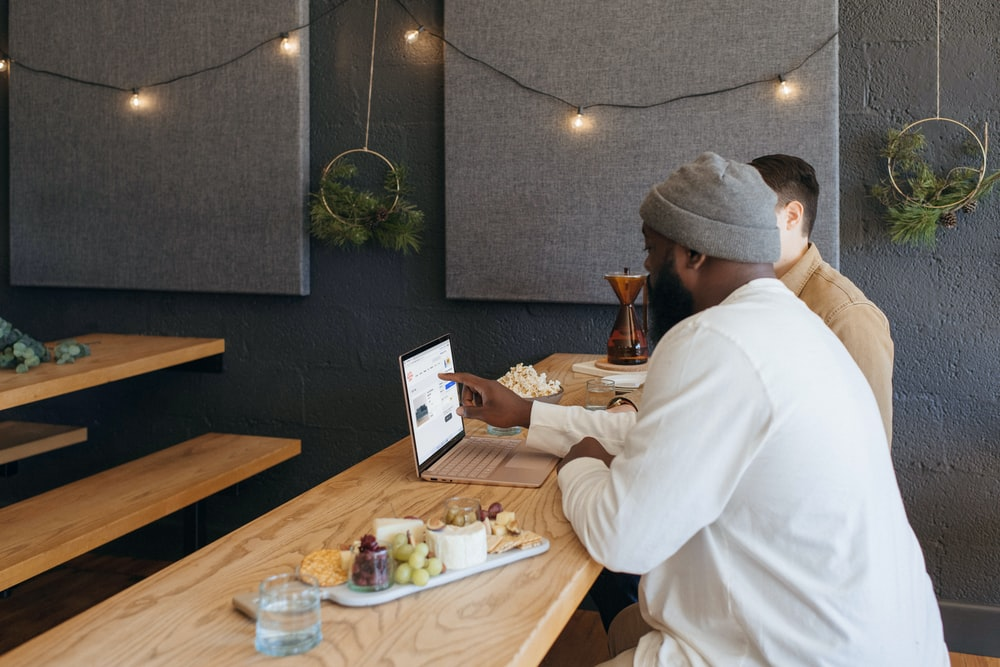 Two people collaborating on their Surface laptop sitting on a table at work