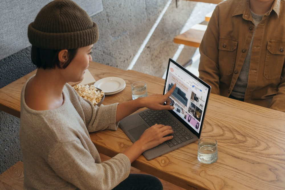 Two people sitting across from each other in an office working on a Surface laptop