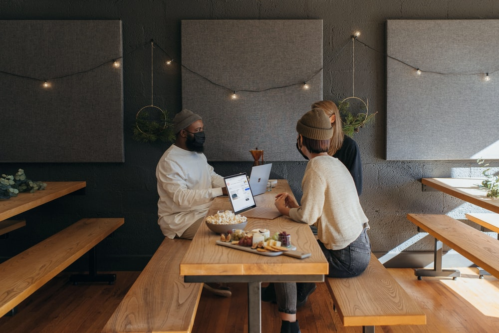 Three people surrounding a table at work wearing masks on their Surface laptops