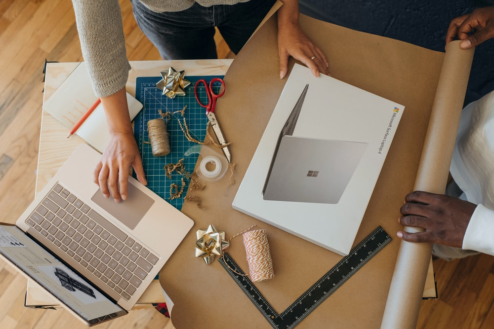 Overhead view of person wrapping a surface laptop box while clicking on a surface laptop