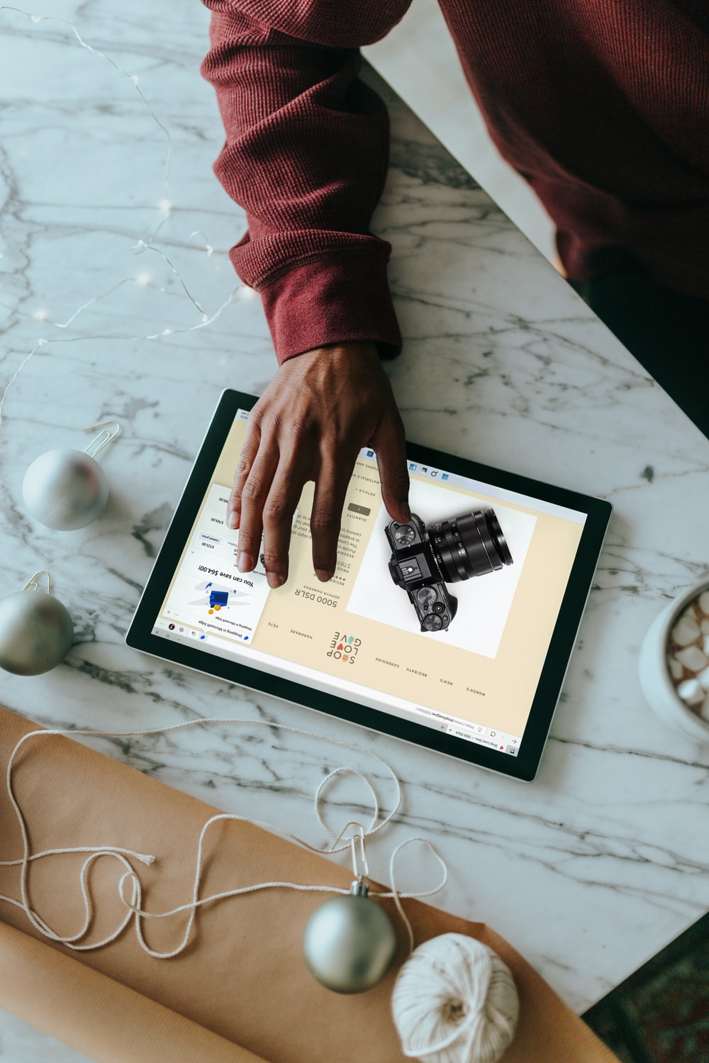 Overhead view of a person clicking on a Surface laptop with wrapping presents around
