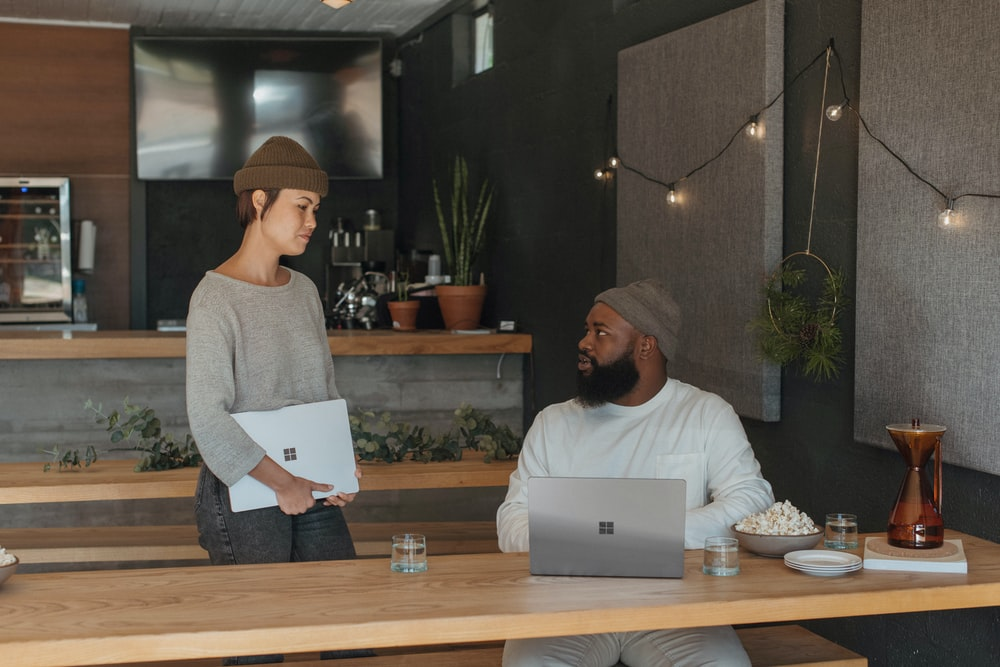 Two coworkers talking at work holding Surface laptops