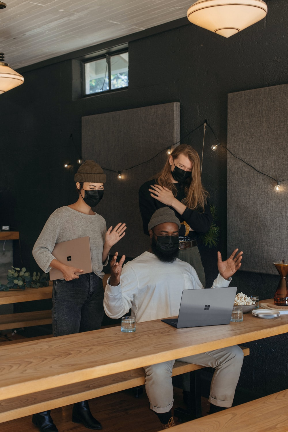 Three coworkers wearing masks talking with someone on video chat in an office