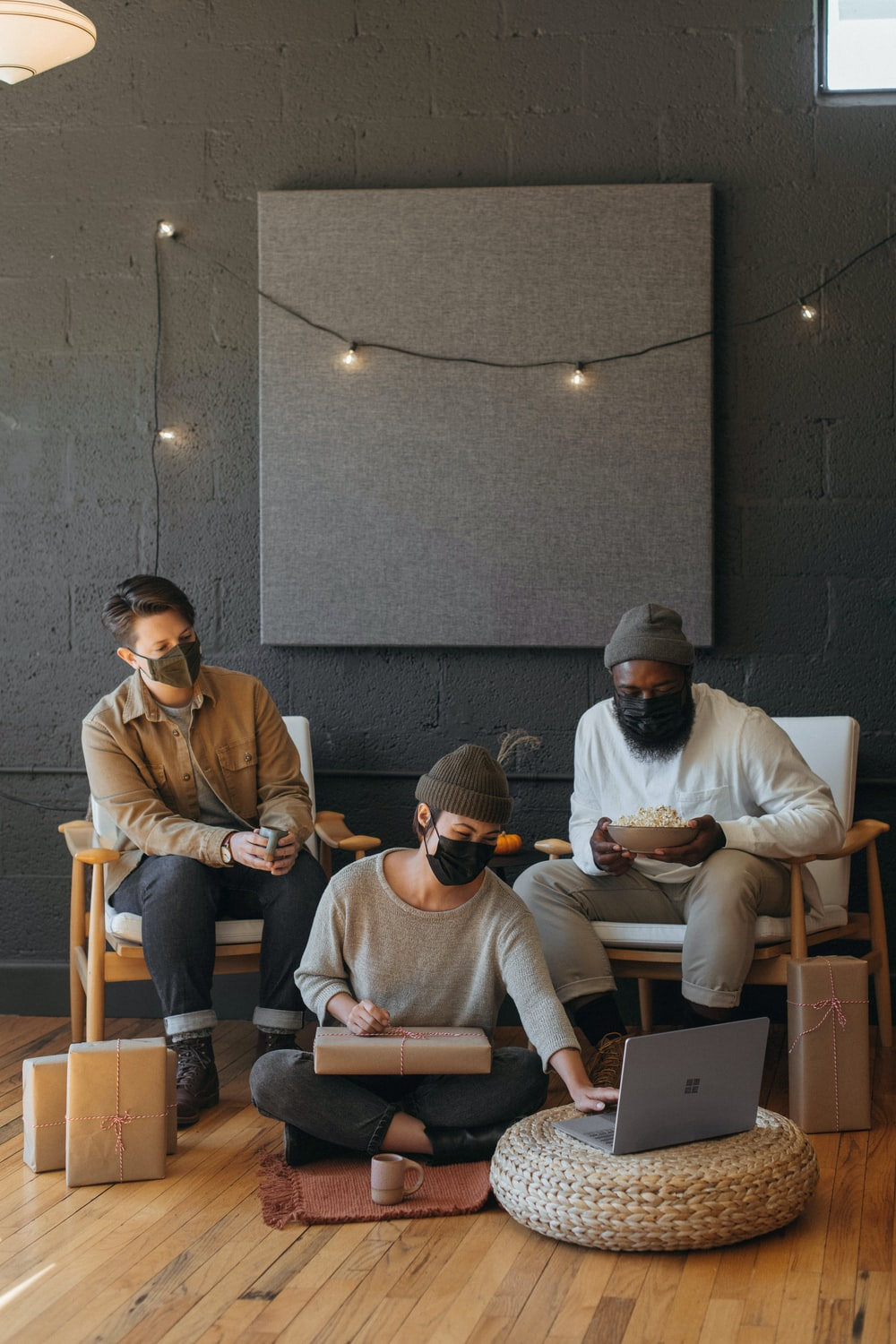 Three coworkers wearing masks on a Surface laptop with Christmas presents on a cart